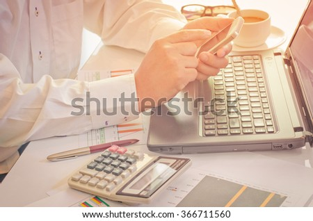 A man working from office using smart phone and notebook computer - stock photo