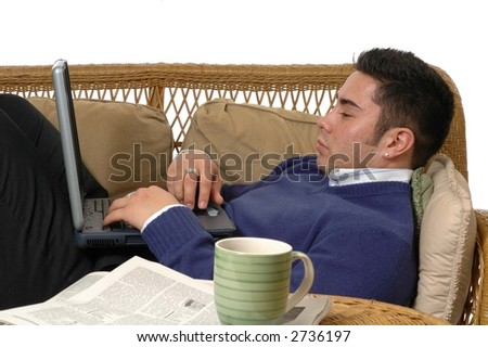 A man working on a laptop computer while laying on the sofa - stock photo