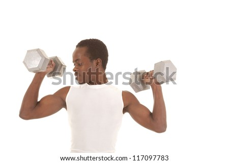 A man working out with big weights doing arm curls looking at his bicep.