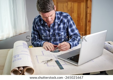 a man working with blueprints and a laptop computer