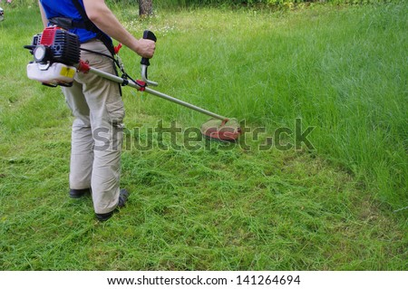 a man working with trimmer cutting grass - stock photo