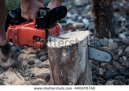 A man works in the forest holding chain saw, ripping the wood block - stock photo