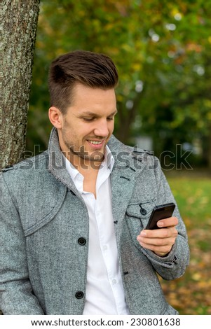a man writes a text message on his cell phone. communication with a smart phone - stock photo