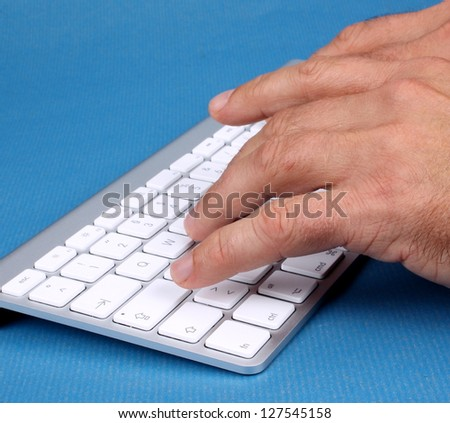 A man writes on PC keyboard on a blue background