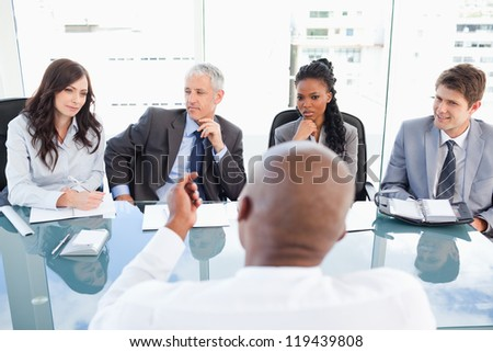 A manager and an employee communicating during a meeting with the full team