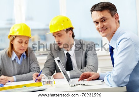 A manager working with laptop, looking at camera and smiling against his colleagues architects - stock photo
