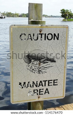A Manatee Caution sign helps protect the endangered West Indian manatees from motorized boats in the Homosassa River, Florida. - stock photo