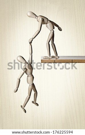 A manikin holding another manikin from falling off a ledge  - stock photo
