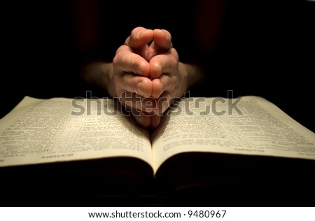 A mans hands clasped in prayer over a  Bible - stock photo