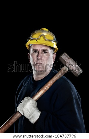A manual laborer with a sledgehammer wearing a yellow hardhat and protective work gloves isolated on black