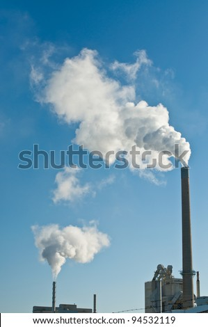 A manufacturing facility pumps smoke into the air from two smokestacks with a clear blue sky in the background.
