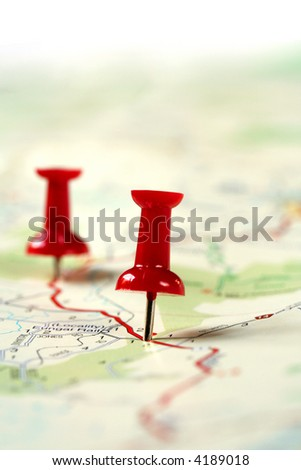A map route marked with red push pins.  Shallow depth of field. - stock photo