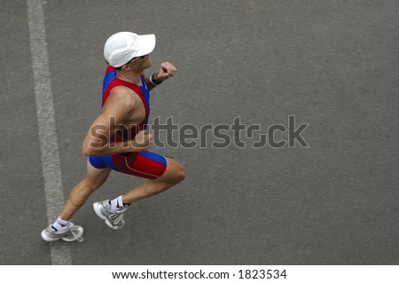 A marathon runner crossing a line, taken from above. Motion blur on his feet. Space for text on the tarmac in front of him.