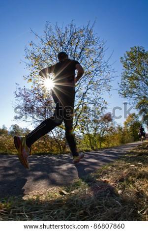 A marathon runner in backlight - stock photo