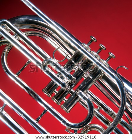 A marching French horn up close isolated against a red  back ground in the square format with copy space. - stock photo