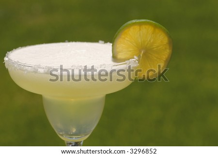 A margarita with a salt rimmed glass and a slice of lime - stock photo