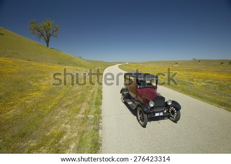 A maroon Model T driving down a scenic road surrounded by spring flowers off of Route 58, Shell Road, CA - stock photo