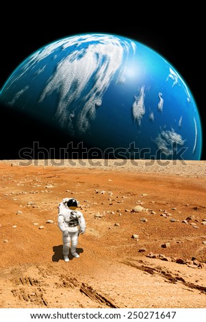A marooned astronaut looks up at an alien sun that illuminates a barren world. A large water covered world with clouds rises in the background. - Elements of this image furnished by NASA.