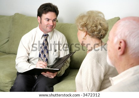 A marriage counselor or salesman listening to an elderly couple.   Could also be a salesman. - stock photo