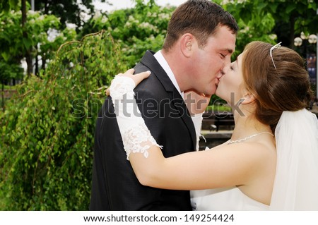 A married couple, bride and groom, about to kiss in sunshine on a beautiful waterfront city