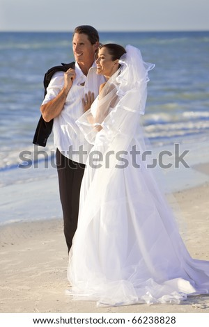 A married couple, bride and groom, together in sunshine on a beautiful tropical beach - stock photo