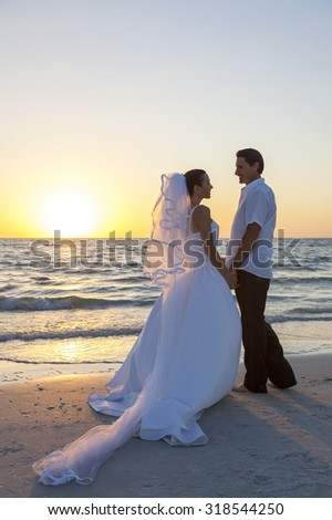 A married couple, bride and groom, together sunset sunrise on a beautiful tropical beach - stock photo