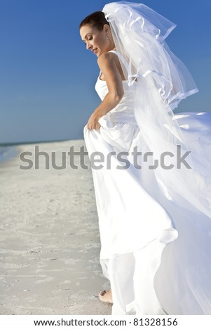 A married woman bride in her wedding dress in sunshine on a beautiful tropical beach - stock photo