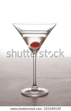 A martini cocktail in a martini glass with a glacier cherry at the bottom  - stock photo