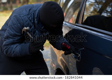 A masked burglar trying to break in a car using a hammer - stock photo