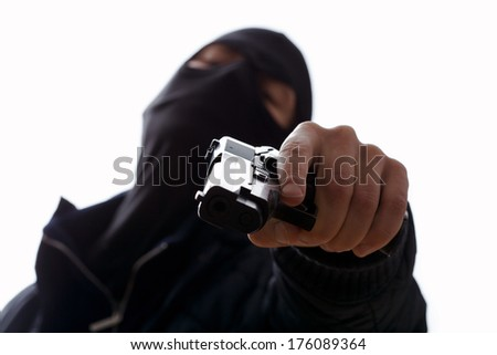 A masked man aiming his gun holding the trigger - stock photo