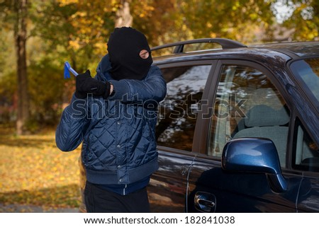 A masked man robbing a car by breaking the window - stock photo