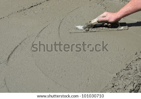 A mason hand finishes a newly poured concrete floor - stock photo