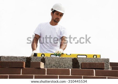 A mason using a level to check his wall  - stock photo
