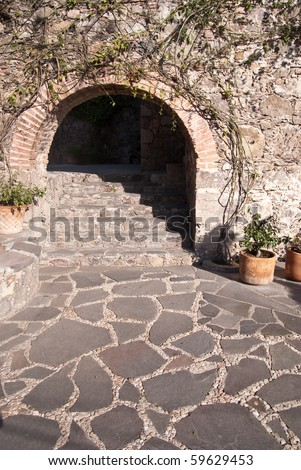 A masonry archway above stone steps and a narrow passageway up a San Miguel de Allende hillside - stock photo