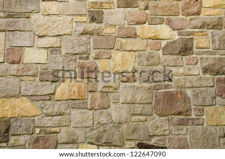 A masonry wall of multicolored stones or blocks - stock photo