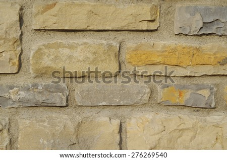 A masonry wall of multicolored stones or blocks - stock photo