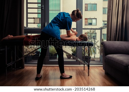 A massage therapist is treating a female client on a table in an apartment - stock photo