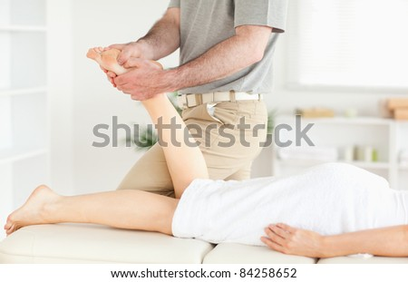 A masseur is massaging a woman's foot in his surgery