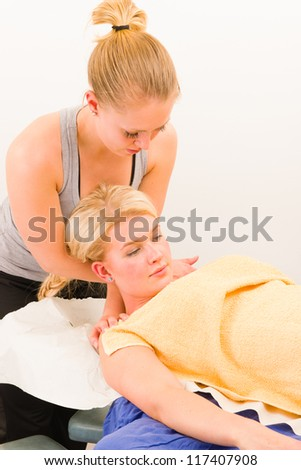 A masseur is stretching a customer's neck - stock photo