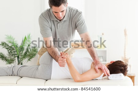 A masseur is stretching a woman's arm