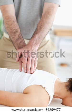 A masseur massages a woman's back in his surgery