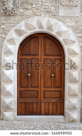 A massive medieval door in the entrance to the church, Italy - stock photo