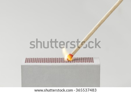 A Match being lit with the striking surface of a matchbox