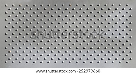 A matt metal plate surface with multiple rivets as textural background.  - stock photo