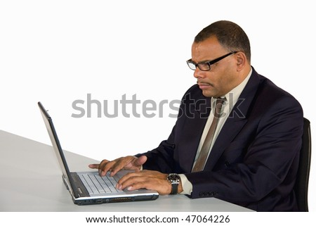 a mature African-American businessman working concentrated at his laptop, isolated on white background