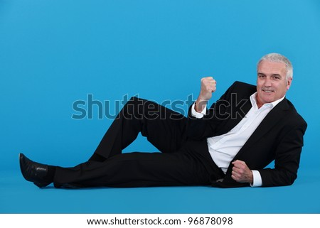 A mature businessman laying on the floor gesturing a yes sign. - stock photo