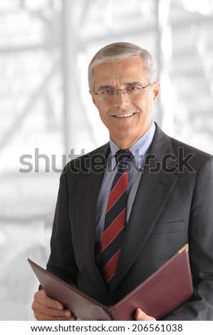 A mature businessman with a leather folder in a modern office building. The background is out of focus and high key. - stock photo