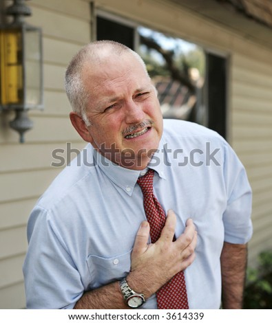 A mature businessman with severe chest pain. - stock photo