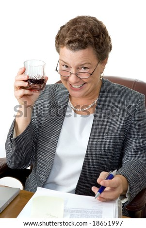 A mature businesswoman drinking on the job, office setting.