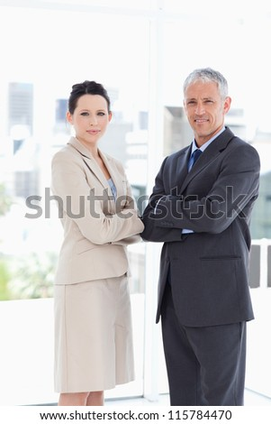 A mature director and his young secretary standing upright in front of the window - stock photo